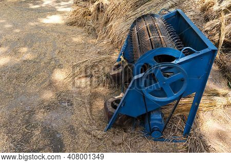 Paddy Threshing Machine With Electric Motor At Farmer's Rice Farm In India Behind Hay Stack