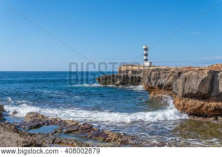 Colonia De Sant Jordi Lighthouse On A Sunny And Winding Day. Mediterranean Sea In The Rocky Coast Of