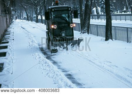 Snowplow Removing Snow On Street After Blizzard. Snowplow Vehicle Clears Snowy Road During Blizzard.