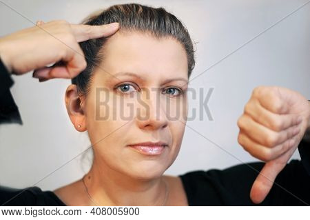 A Woman With A Sad Face On A Gray Background.  She Shows By Finger On The Hair That Becomes Gray. Wo