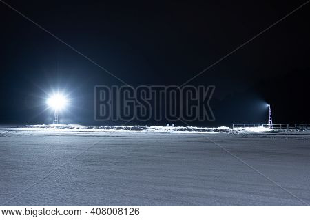 Spotlights Shine On A Snow-covered Field At Night. Two Spotlights Illuminate The Deserted Winter Lan