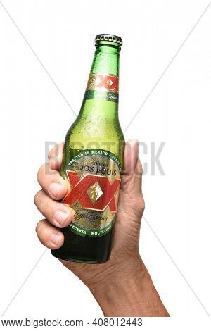 IRVINE, CALIFORNIA - JULY 25, 2019: A hand holding a bottle of Dos Equis Lager over white.