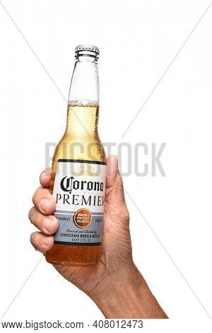 IRVINE, CALIFORNIA - JULY 25, 2019: A hand holding a bottle of Corona Premier Lager over white.