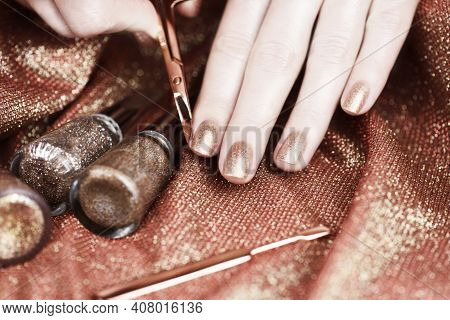 Woman Making Manicure By Herself. Female Hands With Bronze-colored Manicure On A Shiny Bronze Backgr