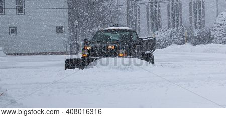 A Private Contracter Is Plowing The Snow In A Parking Lot For The Local Businesses.