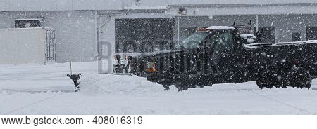 A Black Truck Owned By A Private Contractor Is Plowing The Snow In The Parking Lot Of A Business Dur