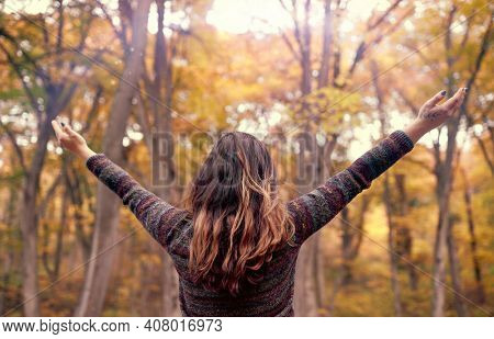 Young woman connecting with nature with open arms showing gratitude for life, Abundance Mindfulness Concept