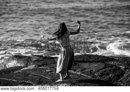 A young dance woman is engaged in choreography on the coast. Black and white photo.