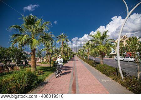Turkey, Alanya - October 20, 2020:Young woman rides a bicycle on Alanya promenade - Ahmet Tokus Bul. in Alanya, Turkey