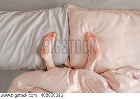 Kids Child Legs Feet Lying On Pillows In Bed At Home. Child Playing Hide And Seek Game Under Blanket