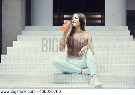 Fitness Woman Drinking Water At Workout In The Gym. Pretty Caucasian Girl Exercising Cross Fitness A