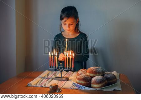 Girl Lighting Candles On Menorah For Traditional Winter Jewish Hanukkah Holiday At Home. Child Celeb