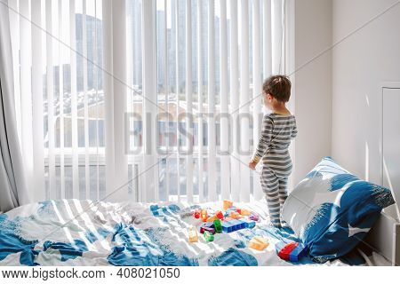 Cute Little Boy Toddler Standing On Bed In Room And Looking Into Window Waiting Expecting Someone. C