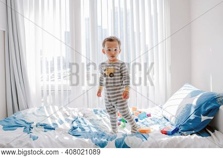 Cute Little Boy Toddler Standing On Bed In Room At Home And Looking At Camera. Adorable Innocent Bab