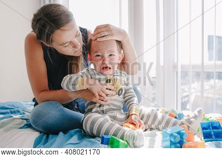 Mother Hugging Pacifying Sad Upset Crying Toddler Boy. Family Young Mom And Crying Baby Sitting On B