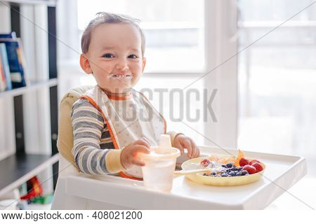 Cute Caucasian Baby Boy Eating Ripe Berries And Fruits With Yogurt. Funny Smiling Child Kid Sitting