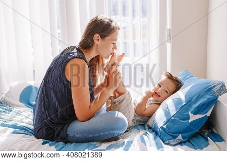 Young Caucasian Mother Kissing Boy Toddler Son Feet Heels Legs. Mom Playing With Child Baby On Bed I