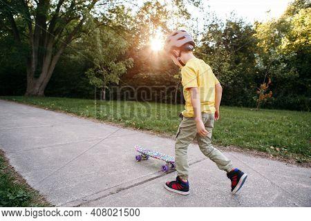 Boy In Grey Helmet Riding Skateboard On Road In Park On Summer Day. Seasonal Outdoor Children Activi