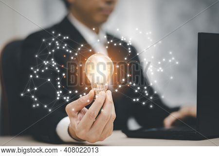 Businessman Hand Holding Light Bulb And Working On The Desk, Creativity And Innovation Are Keys To S