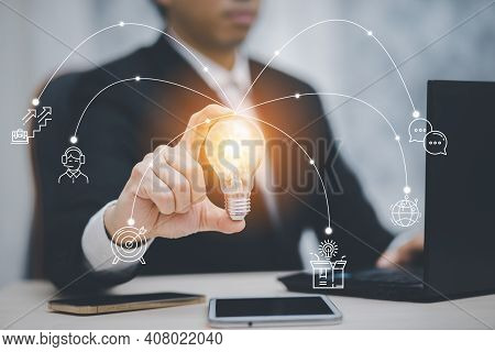 Business Hand Holding Light Bulb And Working With Icon Business With Computer On The Desk, Creativit