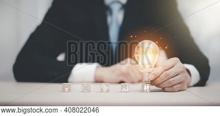 Businessman Hand Holding Light Bulb With Icon On Wood Cube And   Working On Desk, Creativity And Inn