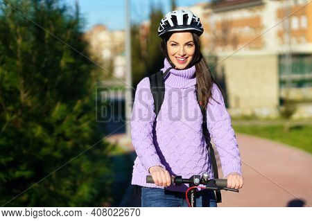 Young Woman In Her Twenties Riding An Electric Scooter Using Helmet.