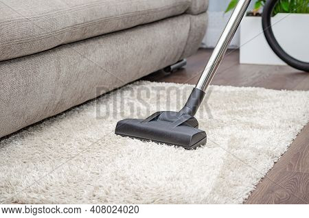A Woman Vacuums A Gray Carpet With A Vacuum Cleaner. Cleaning And Cleanliness Concept