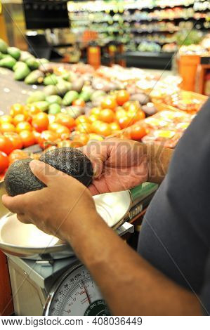 African American Male Buying Produce At A Market Indoors.