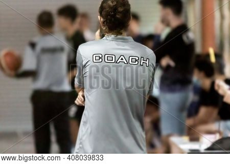 Back Of Male Coach Wearing Grey Coach Shirt Watching His Team Compete, Good For Sport Or Coaching Co