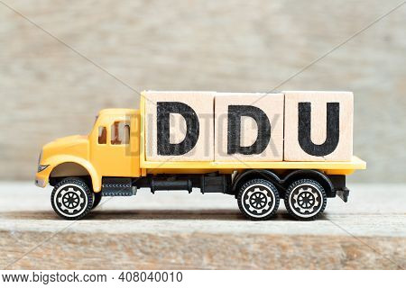 Toy Truck Hold Alphabet Letter Block In Word Ddu (abbreviation Of Delivered Duty Unpaid) On Wood Bac
