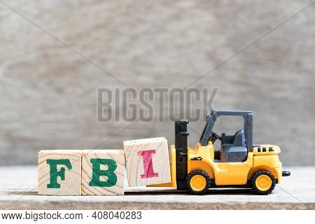 Toy Forklift Hold Letter Block I In Word Fbi (abbreviation Of Federal Bureau Of Investigation) On Wo