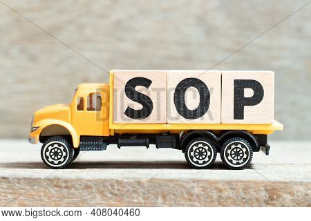 Toy Truck Hold Alphabet Letter Block In Word Sop (abbreviation Standard Operating Procedure) On Wood