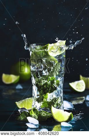 Mojito With Splash And Drops. Cocktail Or Mocktail With Lime, Mint, And Ice In Glass On Blue Backgro