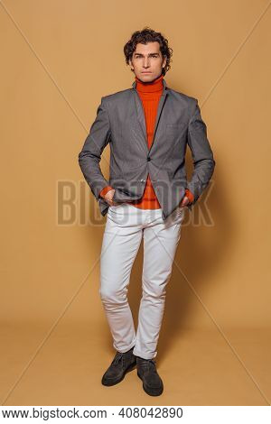 Tall Handsome Man Dressed In Orange Turtleneck, White Jeans And Grey Jacket Posing On The Beige Back