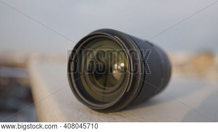 Close-up Of Lens. Action. Lens For Professional Camera On Blurry City Background. Beautiful Wide-ang