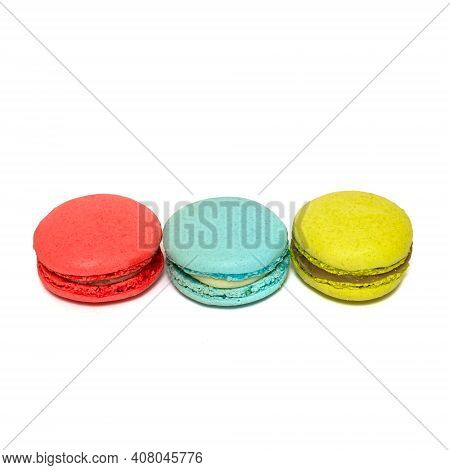 Red Blue Yellow Macaroons Isolated In White Background. Colorful French Macarons Close-up. Tasty Swe