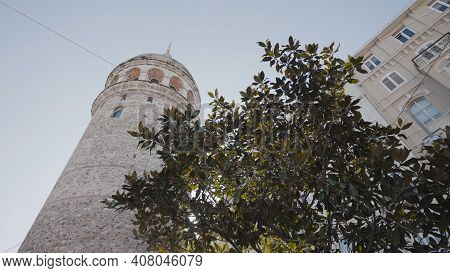 View From Below Of Old Tower In City. Action. Ancient Tower Rises In Center Of City On Background Of