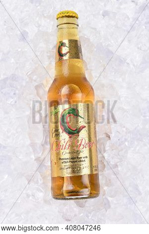 IRVINE, CA - AUGUST 26, 2016: A bottle of Cave Creek Chili Beer on ice. The hot and spicy beer, with a chili in the bottle, is brewed at Cerveceria Mexicana, Tecate, Mexico.