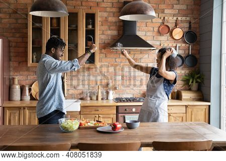 Funny African American Couple Pretending Fighting With Kitchenware, Having Fun