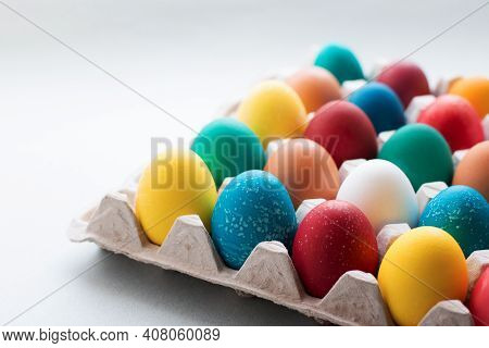 Yellow, Red, Orange, Blue And Green Easter Eggs Painted With Organic Dyes In A Cardboard Tray On A G