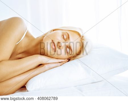 Beautiful Young Woman Sleeping While Lying In Bed Comfortably And Blissfully. Good And Sunny Morning