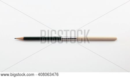 Extend, enlarge, increase, concept image, a short pencil in a wooden pencil extender, isolated on neutral white.