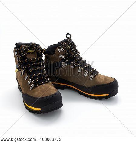Men's Brown Nubuck And Vinyl Trekking Boots. Metal Hardware, Lacing, Yellow Trim, Grooved Sole. Isol