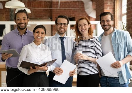 Portrait Of Smiling Multiethnic Colleagues Pose In Office