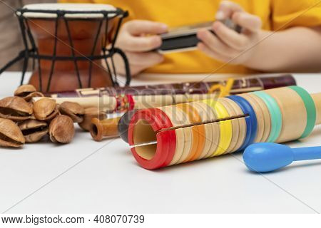 Musical Instruments Close-up: Damaru, Guiro, Noise Percussion, Flute. A Child Learning Musical Instr