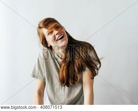 Happy Laughing Long-haired Redhead Young Woman In A Casual T-shirt On A White Background.