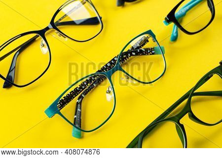 Many Stylish Glasses On A Yellow Background. Health, Style And Business Concept. Eyesight Correction