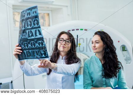 Radiologist With A Female Patient Examining A Ct Scan