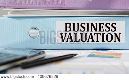 Business Valuation Text Written On Folder With Documents And Calculator.