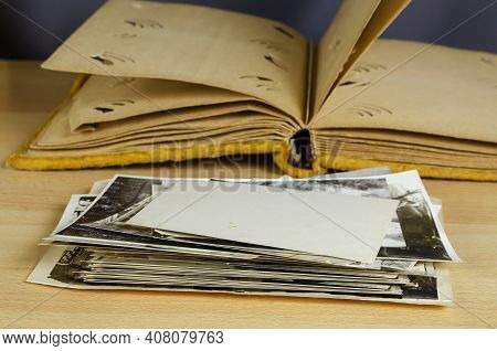 An Open Old Photo Album Wrapped In Yellow Velvet And A Stack Of Black And White Photos In The Foregr